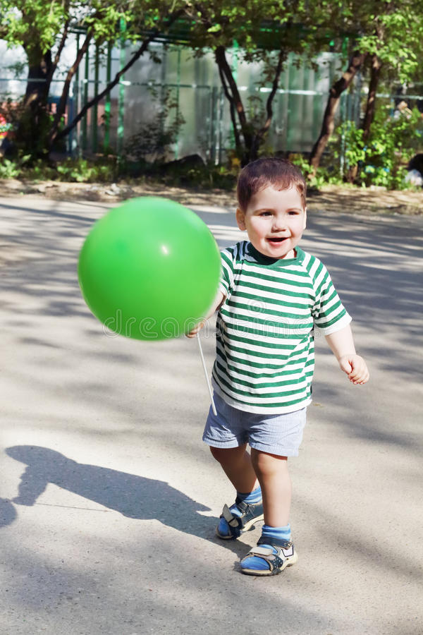 Lycklig liten stilig ballong och leenden för pojkehållgräsplan arkivbild