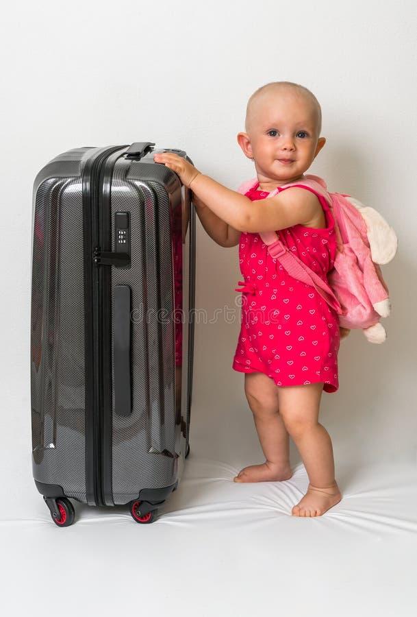 Lycklig liten unge och resväska som isoleras på vit royaltyfria bilder