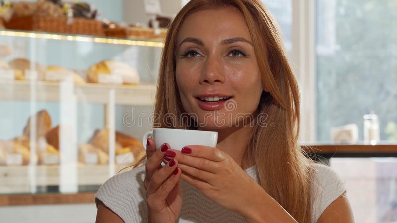 Lycklig ljust rödbrun haired kvinna som glatt ler och att dricka läckert kaffe royaltyfria bilder
