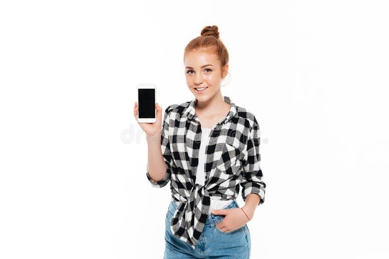 Lycklig ljust rödbrun kvinna i skjorta och jeans royaltyfri foto