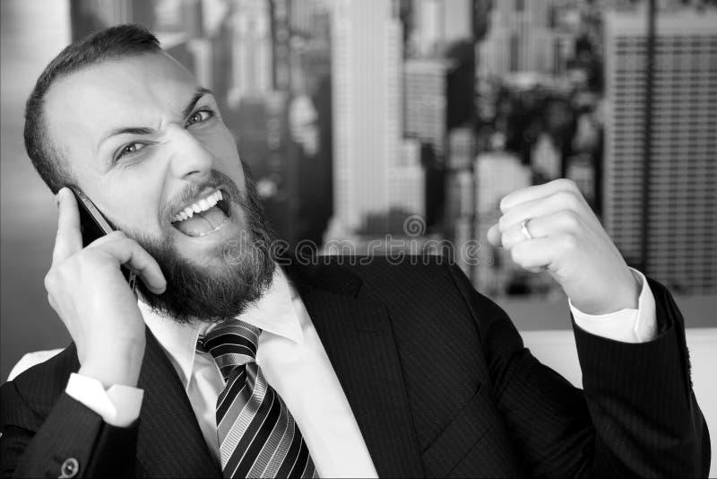 Lycklig lyckad affärsman på telefonen som ser den svartvita kameran arkivbilder