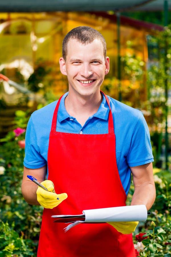 Lycklig lyckad affärsmanträdgårdsmästare i ett växthus royaltyfria bilder