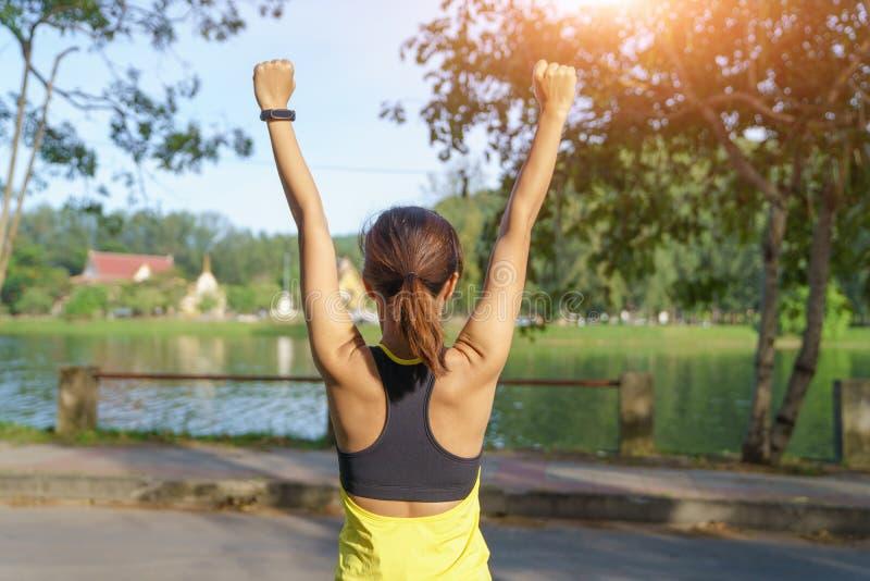 Lycklig lyckad idrottskvinna som lyfter armar till himlen på guld- tillbaka belysningsolnedgångsommar Konditionidrottsman nen med arkivfoton