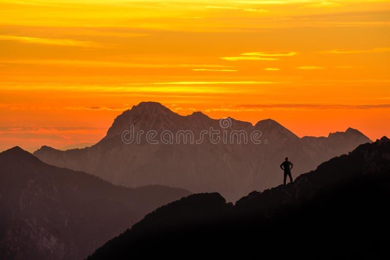 Lycklig lyckad vinnande man som når bergtoppmötet I lager bergskedjakonturer för imponerande föreställning med apelsinen fotografering för bildbyråer