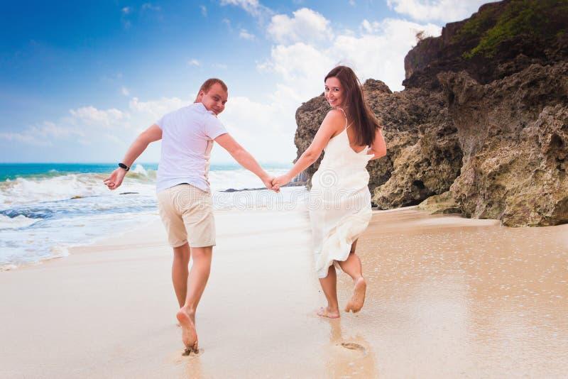 Lycklig lycklig spring för iklädd vit för folk på stranden royaltyfri fotografi