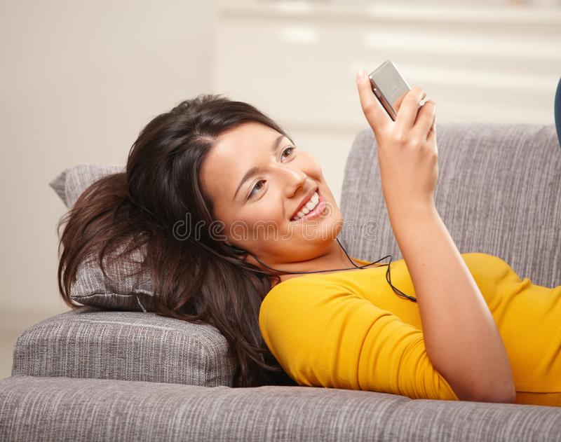 lycklig lyssnande musiktelefon för flicka till royaltyfri bild