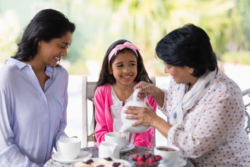 Lycklig mång--utveckling familj som har frukosten tillsammans arkivbild