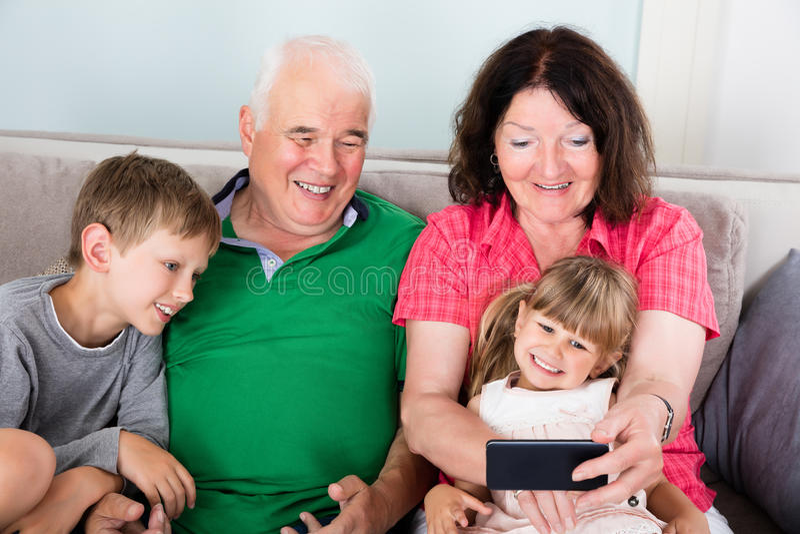 Lycklig mång- utvecklingsfamilj som hemma tar bilden arkivfoto
