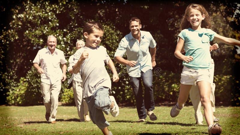 Lycklig mång- utvecklingsfamilj som springer in mot kamera arkivfoton