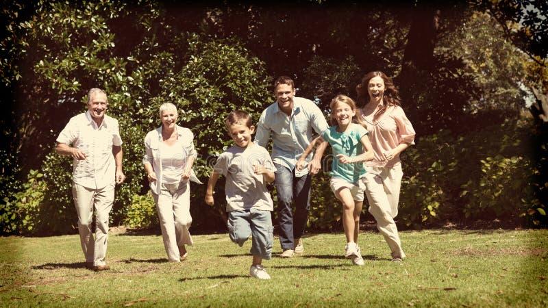 Lycklig mång- utvecklingsfamiljspring in mot kamera royaltyfri fotografi