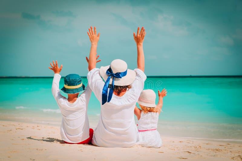 Lycklig mamma med son- och dotterhänder upp på stranden royaltyfri bild