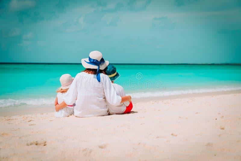 Lycklig mamma med son- och dotterkramen på stranden arkivfoton
