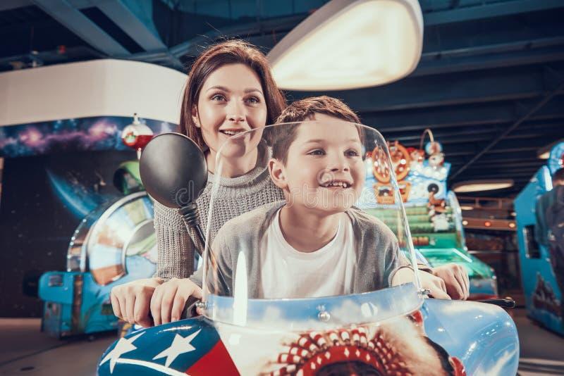 Lycklig mamma och son på leksakmotorcykeln royaltyfria foton