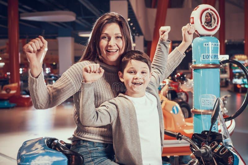 Lycklig mamma och son på leksakmotorcykeln arkivfoton