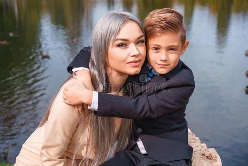 Lycklig mamma och son som utomhus kramar vid sjön royaltyfria bilder