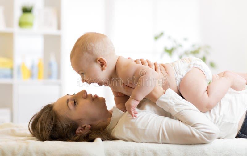 Lycklig mamma som spelar med hennes unge i säng som tycker om solig morgon i hem- sovrum royaltyfri bild