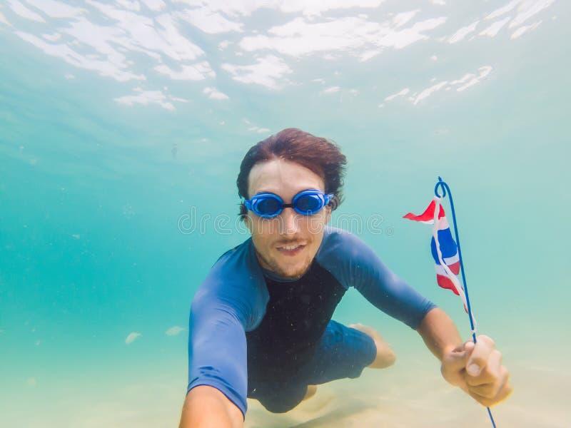 Lycklig man, i att snorkla maskeringsdyken som är undervattens- med tropiska fiskar med den Thailand flaggan i pöl för hav för ko arkivfoton