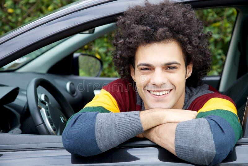Lycklig man i bil som ler se kameran arkivfoton