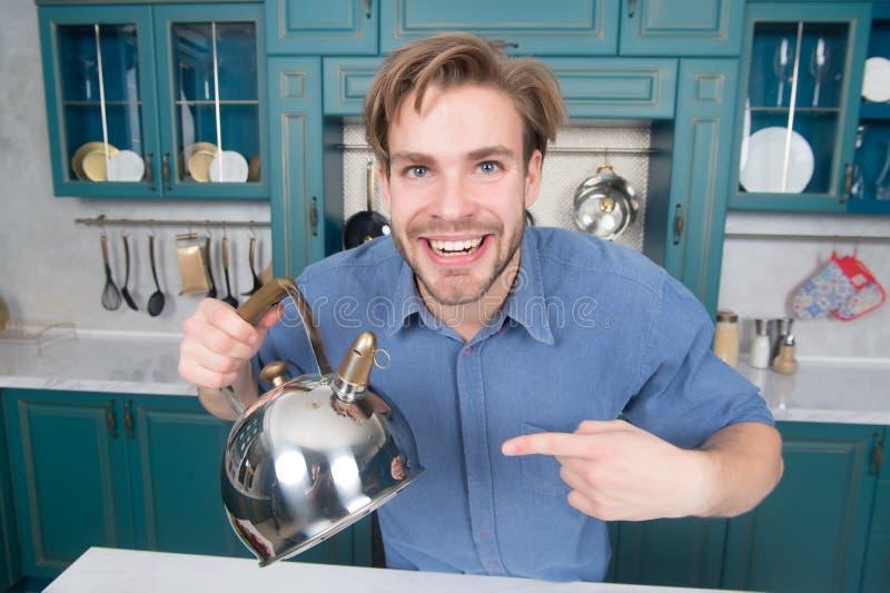 Lycklig man i blått skjortapunktfinger på kokkärlet royaltyfria bilder