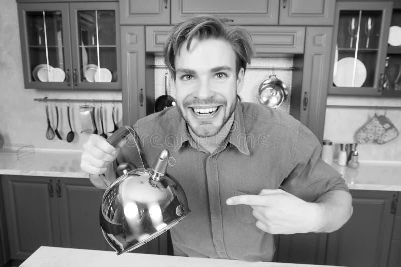 Lycklig man i blått skjortapunktfinger på kokkärlet royaltyfri fotografi