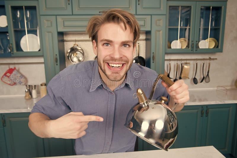 Lycklig man i blått skjortapunktfinger på kokkärlet arkivfoto