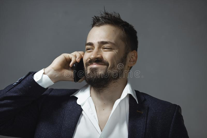 Lycklig man i dräkt som talar på Smartphone arkivbild