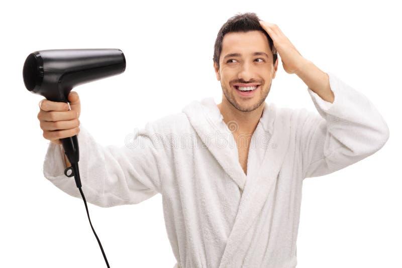 Lycklig man i en badrock som torkar hans hår med en hårtork royaltyfri bild