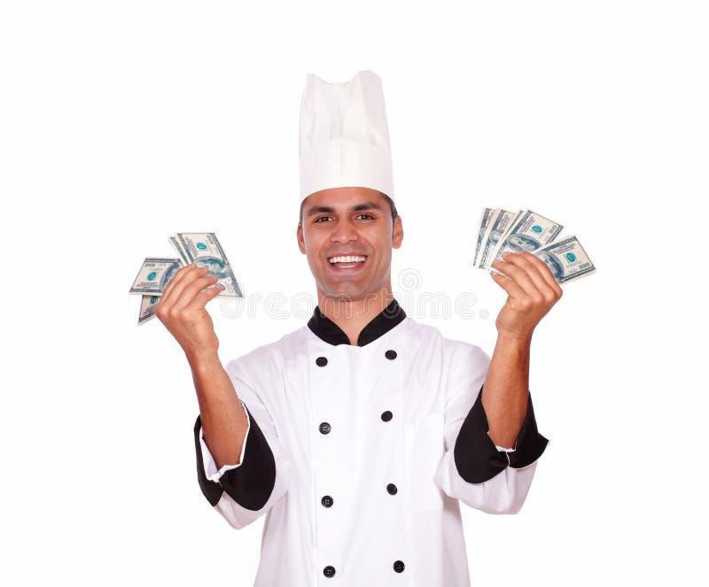 Lycklig man i enhetliga hållande pengar för kock royaltyfri bild