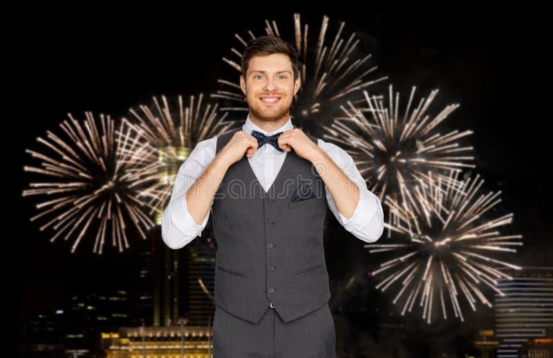 Lycklig man i festlig dräkt över fyrverkerit i stad royaltyfri foto