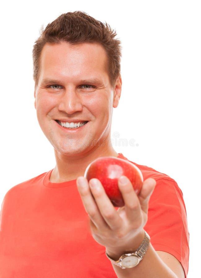Lycklig man i hållande äpple för röd skjorta. Banta sund näring för hälsovård. royaltyfri bild