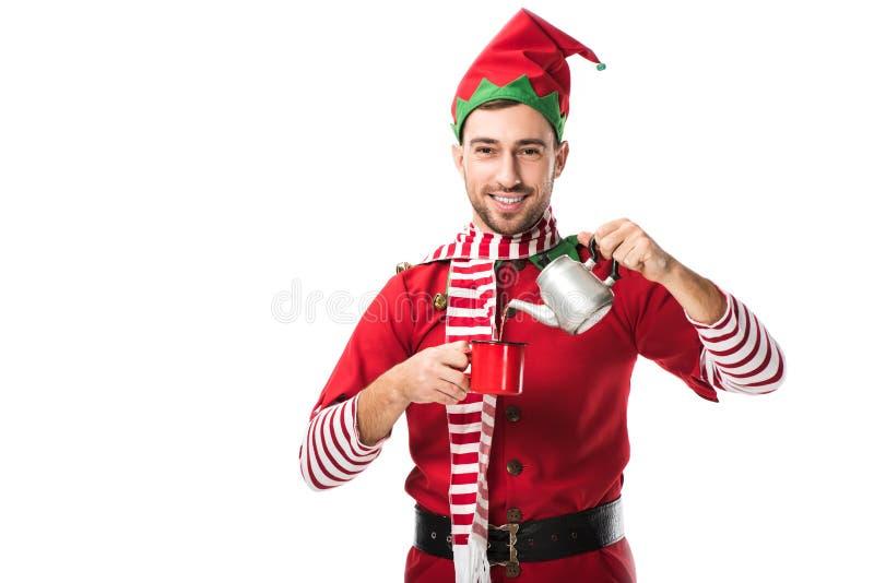 lycklig man i julälvadräkt med hällande te för metallkokkärl i kopp och se den isolerade kameran royaltyfria bilder