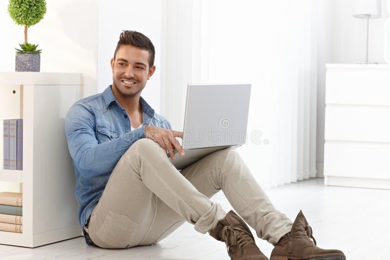 Lycklig man med bärbara datorn arkivfoto