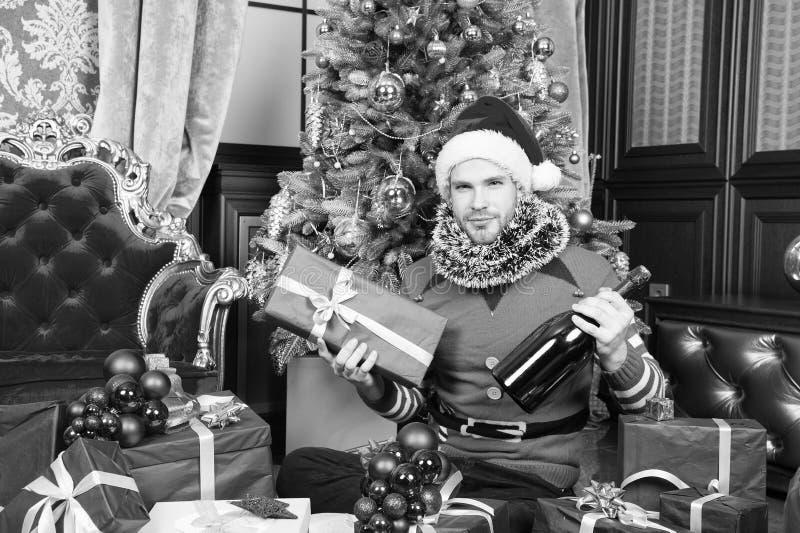 Lycklig man med den n?rvarande asken och champagne p? jultr?det Man i den Santa Claus dr?kten med julg?va T?nd upp arkivbild