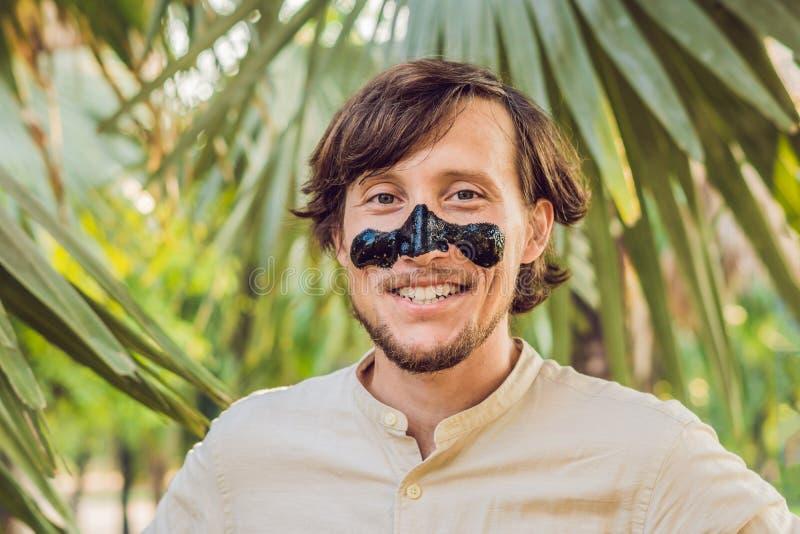 Lycklig man med den svarta maskeringen på framsidan Foto av behandlingar för manhäleribrunnsort Begrepp för skönhethudomsorg arkivfoto