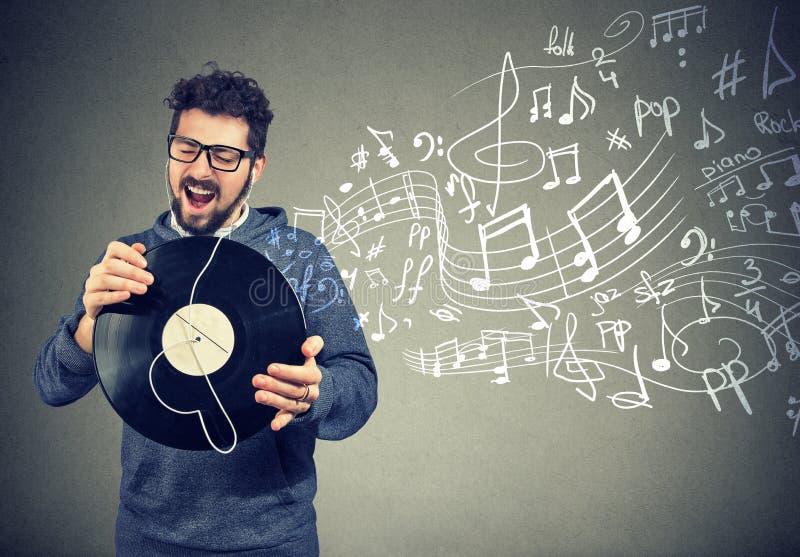 Lycklig man med disketten för vinylrekord som lyssnar till musik arkivfoton