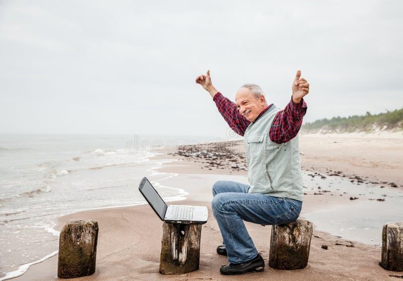 Lycklig man med en bärbar dator på stranden royaltyfri foto