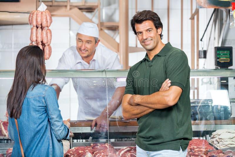 Lycklig man med kvinnaköpandekött på slakt arkivfoto