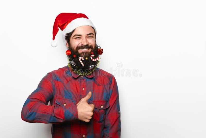 Lycklig man med skägget och julgarneringar som visar upp tummen arkivbild