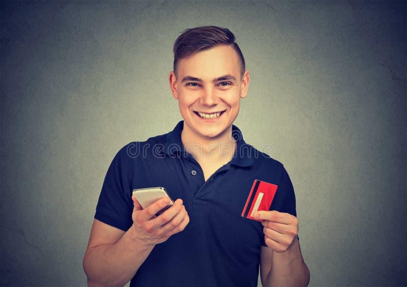 Lycklig man med smartphonen och kreditkorten royaltyfri fotografi