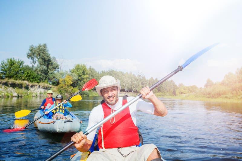 Lycklig man med två ungar som tycker om kajakritt på den härliga floden Fader med pys- och tonåringflickan som kayaking på varmt arkivfoton