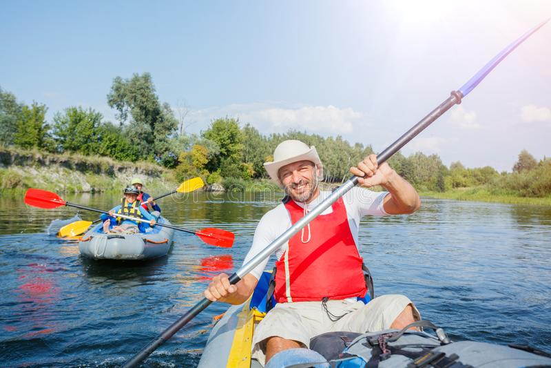 Lycklig man med två ungar som tycker om kajakritt på den härliga floden Fader med pys- och tonåringflickan som kayaking på varmt royaltyfria bilder