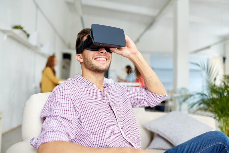 Lycklig man med virtuell verklighethörlurar med mikrofon på kontoret royaltyfria bilder