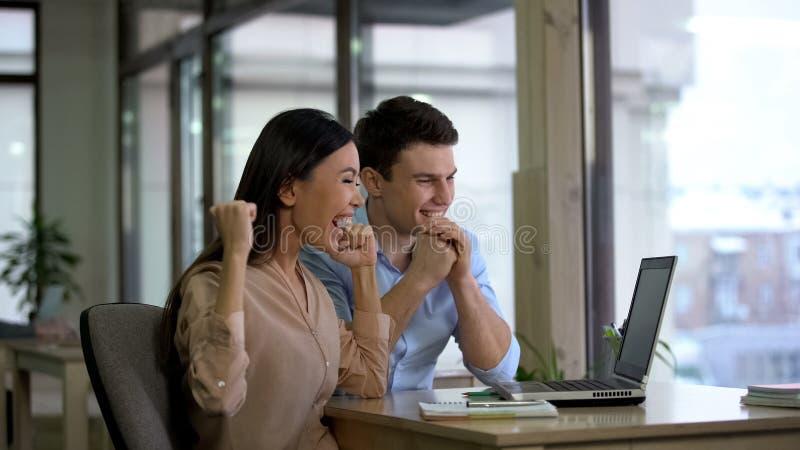 Lycklig man och affärskvinna som i regeringsställning läser bärbar datoremailen, arbetsbefordran arkivbilder