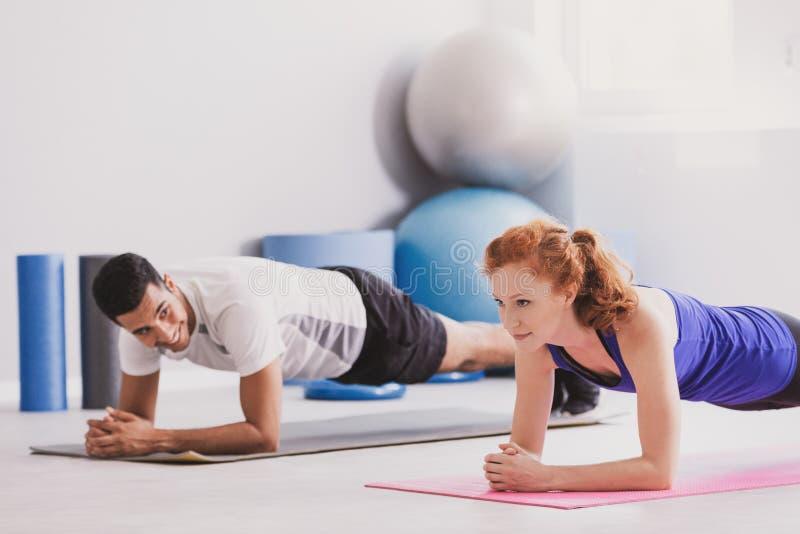 Lycklig man och idrottskvinna som övar på mattt under gymnastik royaltyfri fotografi