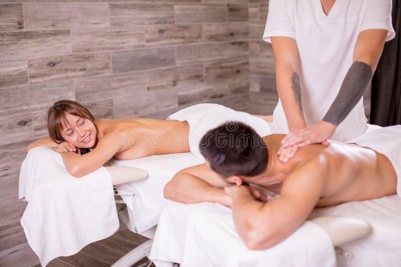 Lycklig man och kvinna som får massagetogeher arkivbild
