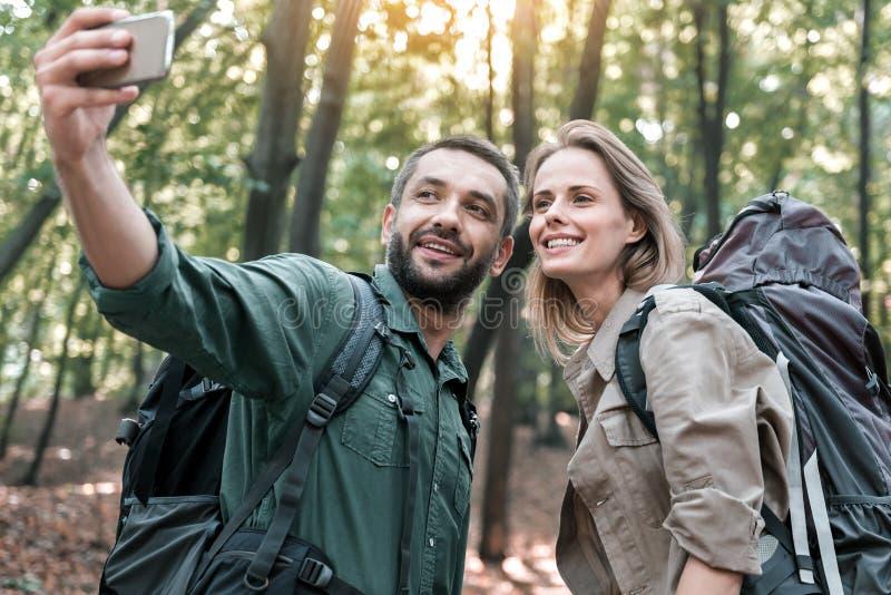 Lycklig man och kvinna som fotograferar sig på smartphonen i natur fotografering för bildbyråer