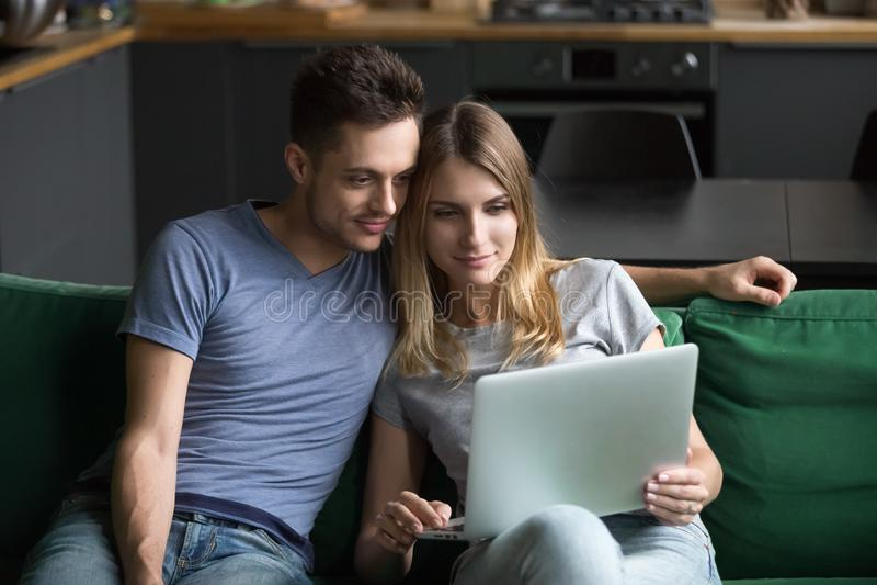 Lycklig man och kvinna som tillsammans sitter och använder bärbara datorn arkivbild
