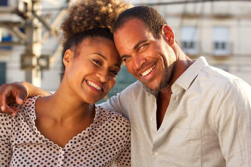 Lycklig man och kvinna som tillsammans står i stad på datum royaltyfri fotografi