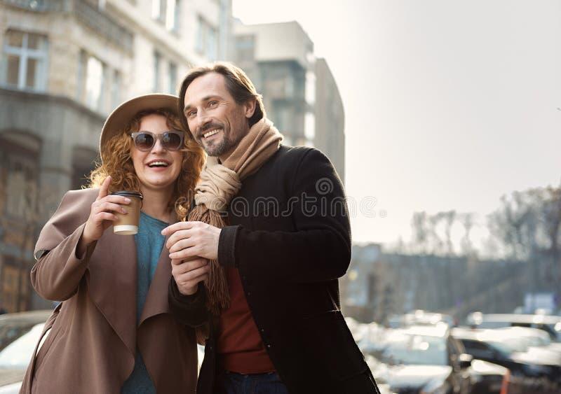 Lycklig man och kvinna som tycker om kaffe på gatan royaltyfria bilder