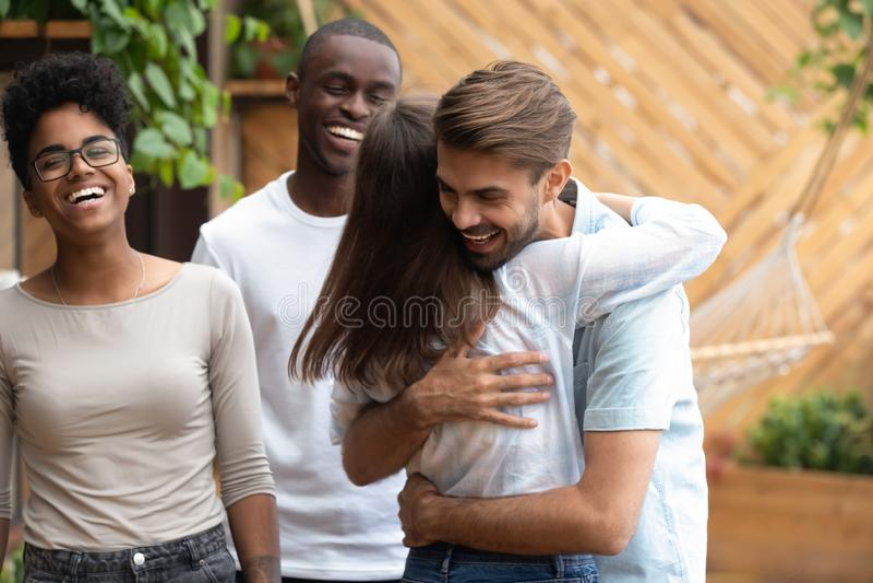 Lycklig man- och kvinnahälsning som kramar på mång--person som tillhör en etnisk minoritet vänmöte fotografering för bildbyråer